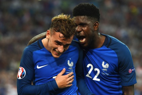 France's defender Samuel Umtiti (R) celebrates with forward Antoine Griezmann after he scored a penalty shot giving France the first goal of the match during the Euro 2016 semi-final football match between Germany and France at the Stade Velodrome in Marseille on July 7, 2016. / AFP PHOTO / PATRIK STOLLARZ